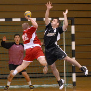 A handball player jumps in the air to shoot as the goalie and a defender try to block the shot.