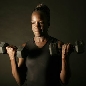 A female lifting free weights in front of a black background.