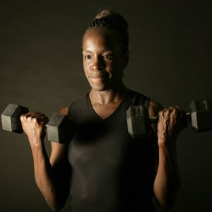 A woman lifts weights in front of a black background.