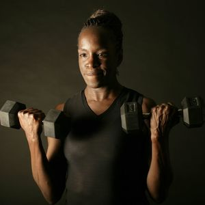 A woman lifting weights in front of a black background.