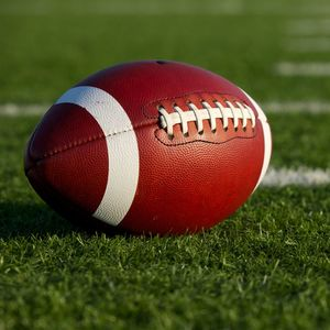 A football sitting on a turf field.