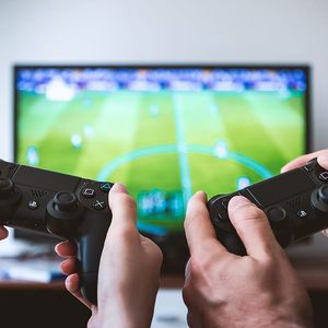 Hands holding video game controllers in front of a TV.