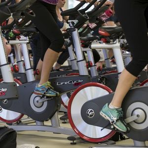 Shots of the lower half of stationary bikes during a group fitness cycling session.
