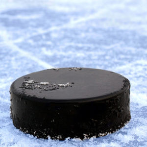 A hockey puck sitting on ice.