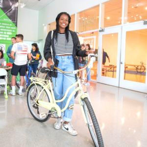 student stands with student at secondhand bike sale