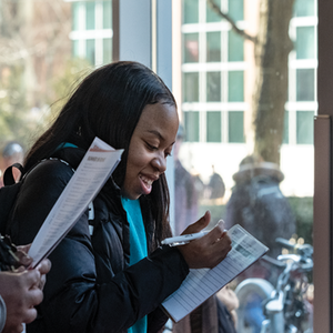 student reading brochure at study abroad fair