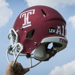 Hand holding the Temple red football helmet
