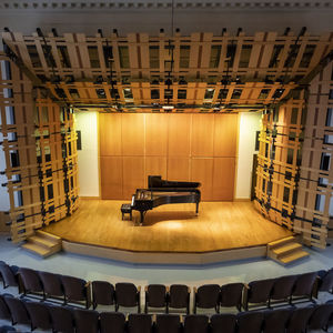 Rock hall auditorium with a lit stage featuring a single piano
