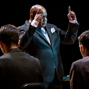 close-up of conductor standing in front of two jazz musicians