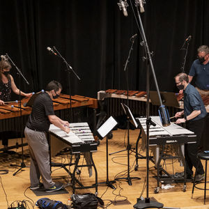 4 people playing various percussion instruments on a stage set up with microphones and recording equipment