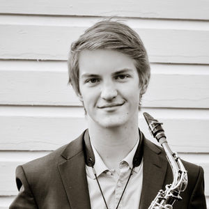black and white photo of young man wearing a suit jacket and holding a saxophone