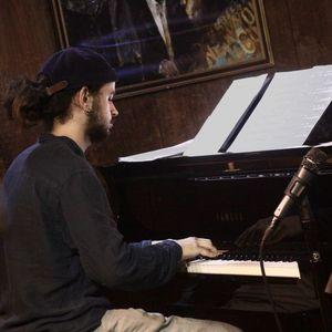 man in a dark shirt and baseball cap playing piano