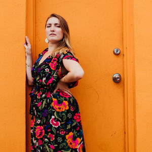 woman in a floral dress standing in front of a bright orange doorway
