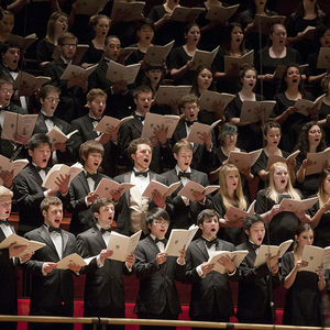 dozens of singers, dressed in formal black, singing and holding music