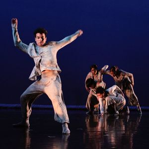 5 dancers in drab white costumes against a dark blue background