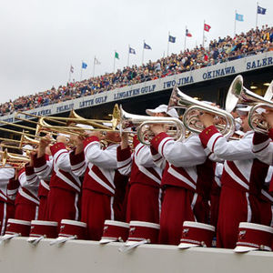 Marching band members in a stadium stands wearing red and white uniforms holding trumpets