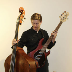 man in a black shirt looking down, holding a double bass in one hand and an electric guitar in the other
