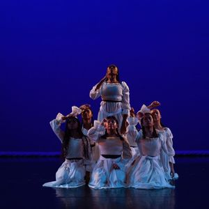 7 dancers in white dresses, kneeling closely together on a stage with a blue backdrop