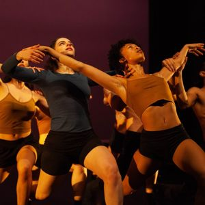 dancers wearing brown and black posing on a dimly lit stage