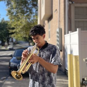 Man standing outside on the sidewalk playing a trumpet
