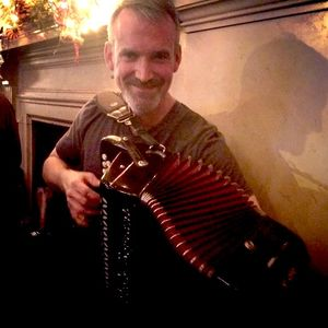 man smiling and playing an accordion