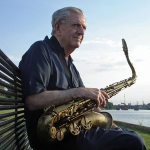 man sitting on a bench outside holding a saxophone