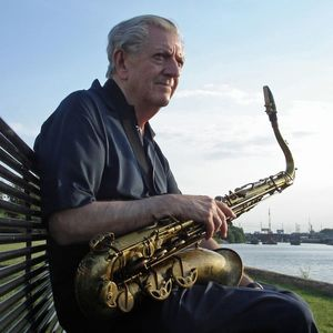 man sitting on a bench on a sunny day holding a saxophone