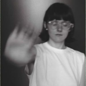 Black and white photo of woman with short dark hair, glasses, and a white tshirt, standing with her right arm out. her hand is blurred as if in motion