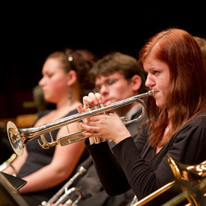red-haired woman playing trumpet with other band members in background