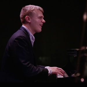 Blond man in a black suit smiling and playing the piano