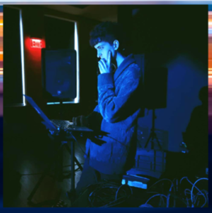 man standing in a dark room lit by a blue screen, looking at some recording equipment