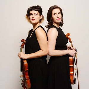 two women in black dresses standing back to back holding violins