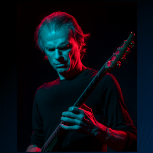 Close-up of man playing an electric guitar on a dark stage lit by blue and red light