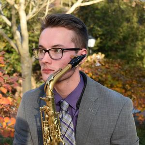man in a grey jacket, purple shirt, and glasses, holding a saxophone with a backdrop of autumn leaves