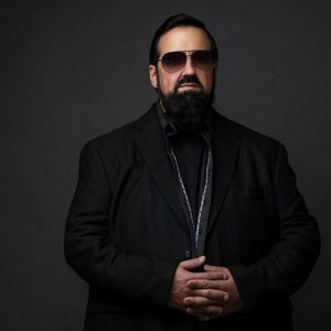 man with a long black beard, a black suit, and black aviator sunglasses standing with his hands folded