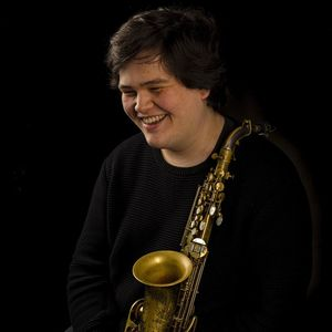 smiling man in a black sweater holding a saxophone
