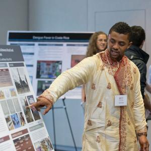 student presents a poster at Global Temple 2014